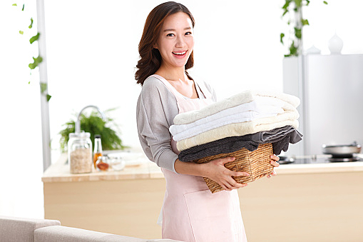 Portrait of young woman holding stack of towels